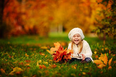 La ragazza del bambino ha divertimento con i fogli dorati caduti Immagini Stock Libere da Diritti