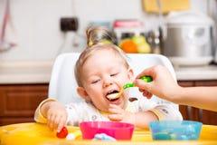 La ragazza del bambino mangia il porridge da un cucchiaio sulla cucina fotografie stock libere da diritti