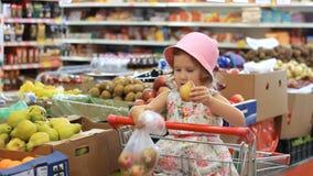 La ragazza del bambino nel deposito sceglie le pere della frutta Supermercato della drogheria e carrello di acquisto archivi video