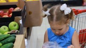 La ragazza del bambino nel supermercato compra la frutta - mele Acquisto del bambino archivi video