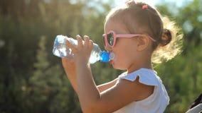 La ragazza del bambino in occhiali da sole beve l'acqua da una bottiglia Primo piano del bambino del ritratto un giorno soleggiat archivi video