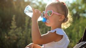La ragazza del bambino in occhiali da sole beve l'acqua da una bottiglia Primo piano del bambino del ritratto un giorno soleggiat video d archivio