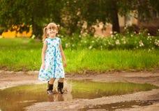 La ragazza del bambino passa una pozza Estate immagine stock