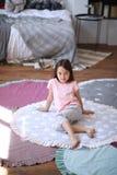 La ragazza del bambino si siede sul pavimento sulla stuoia rotonda fotografia stock