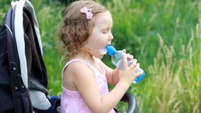 La ragazza del bambino si siede in un passeggiatore di bambino e beve l'acqua da una bottiglia stock footage