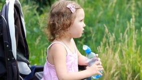 La ragazza del bambino si siede in una carrozzina e beve l'acqua da una bottiglia stock footage