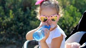 La ragazza del bambino si siede in una carrozzina e beve l'acqua da una bottiglia Sete di estate Primo piano del ritratto del bam video d archivio