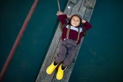 La ragazza del bambino si trova sul ponte di legno e sui sorrisi su fondo di riv fotografia stock