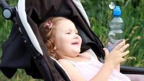 La ragazza del bambino si trova in una carrozzina e beve l'acqua da una bottiglia Sete di estate video d archivio
