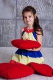 La ragazza del bambino sta giocando con il pulcino che si siede sul cuscino Fotografie Stock Libere da Diritti