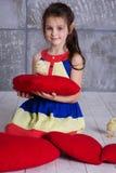 La ragazza del bambino sta giocando con il pulcino che si siede sul cuscino rosso Fotografia Stock