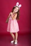 La ragazza del bambino sta indossando le orecchie rosa con i regali Immagine Stock
