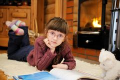 La ragazza del bambino sta leggendo davanti al camino Fotografie Stock