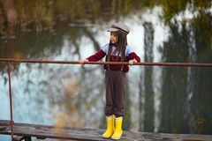 La ragazza del bambino sta sul ponte di legno su fondo del fiume fotografia stock libera da diritti