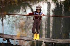 La ragazza del bambino sta sul ponte di legno su fondo del fiume immagine stock
