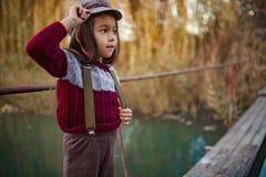 La ragazza del bambino sta sul ponte di legno su fondo del fiume fotografia stock