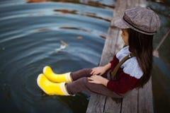 La ragazza del bambino in stivali di gomma gialli si siede sul ponte di legno e mette fotografia stock