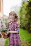 La ragazza del bello bambino con il canestro della campanula fiorisce nel giardino di primavera Immagini Stock Libere da Diritti