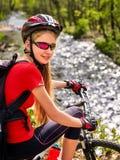 La ragazza del ciclista delle bici guida le montagne della bicicletta Donna su alpinismo del veicolo Fotografie Stock Libere da Diritti