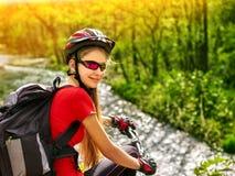 La ragazza del ciclista delle bici guida le montagne della bicicletta Donna su alpinismo del veicolo Immagini Stock Libere da Diritti