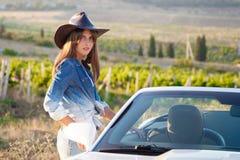 La ragazza del cowboy sta al convertibile Fotografia Stock Libera da Diritti
