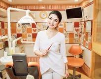La ragazza del dentista dei bambini all'ufficio del dentista tiene il vostro spazzolino da denti fotografie stock