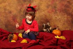 La ragazza del diavolo sta divertendosi per Halloween con le zucche ed il cappello Fotografia Stock Libera da Diritti