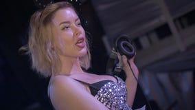 La ragazza del DJ in orecchie di topo balla alla piattaforma girevole randello Movimento lento cuffie stock footage