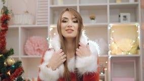 La ragazza del fascino si è vestita nel vestito di Santa che posa e che flirta vicino alle decorazioni in 4K stock footage