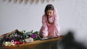 La ragazza del fiorista scrive le note in un taccuino dietro il contatore immagine stock libera da diritti