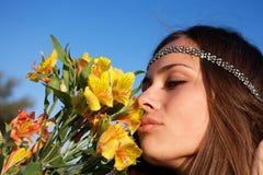 La ragazza del Hippie sente l'odore del giglio Immagini Stock Libere da Diritti