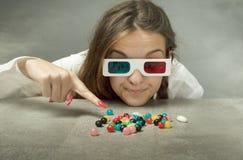 La ragazza del nerd con i vetri 3d ha indicato la caramella immagine stock libera da diritti