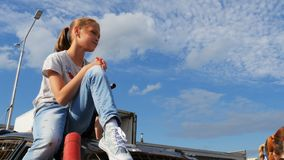 La ragazza del primo piano si siede sul veicolo fra la gioventù sotto cielo blu video d archivio