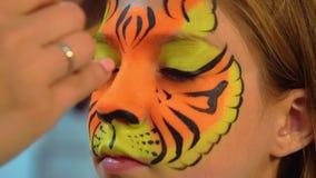 La ragazza del ritratto che riceve il body art sul fronte gradisce la tigre Aquagrum del fronte della tigre del primo piano stock footage