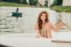 la ragazza del ritratto sta sedendosi in una barca bianca sul fiume nella distanza una vede una barca riservata con un rematore fotografie stock libere da diritti