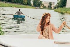 la ragazza del ritratto sta sedendosi in una barca bianca sul fiume nella distanza una vede una barca riservata con un rematore fotografie stock