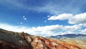 La ragazza del viaggiatore in cappelli si siede sull'orlo di una montagna rossa C'è paesaggio scenico e cielo nuvoloso nei preced archivi video