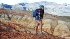 La ragazza del viaggiatore con lo zaino negli shorts dei jeans e in sneackers sta stando su una collina rossa C'è scenico irreale stock footage
