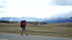 La ragazza del viaggiatore con uno zaino sta camminando dal lato della strada della montagna Ci sono montagne della neve nei prec video d archivio