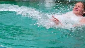 La ragazza dell'adolescente in costume da bagno nuota in stagno con i getti di acqua archivi video