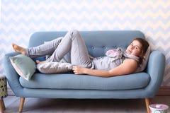 La ragazza dell'adolescente mette sul sofà in pigiama Immagini Stock