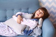 La ragazza dell'adolescente mette sul sofà in pigiama Immagini Stock Libere da Diritti