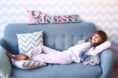La ragazza dell'adolescente mette sul sofà in pigiama Fotografia Stock