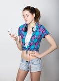 La ragazza dell'adolescente negli shorts del denim e una camicia di plaid che parlano sul telefono cellulare ed esprimono le emoz Immagini Stock Libere da Diritti