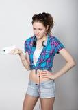 La ragazza dell'adolescente negli shorts del denim e una camicia di plaid che parlano sul telefono cellulare ed esprimono le emoz Fotografia Stock