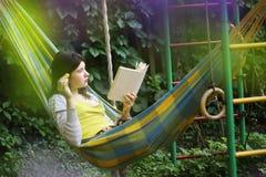 La ragazza dell'adolescente risiede in amaca con il libro ed il gattino Fotografie Stock Libere da Diritti