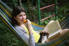La ragazza dell'adolescente risiede in amaca con il libro, il gattino e l'albicocca Fotografia Stock Libera da Diritti
