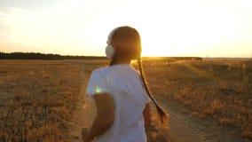 La ragazza dell'adolescente si prepara al tramonto ed ascolta musica, sport che la ragazza in cuffie fa pareggiare stock footage