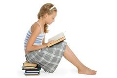 La ragazza dell'adolescente si siede sul libro di lettura e del pavimento Immagini Stock