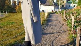 La ragazza dell'adolescente in un cappotto grigio cammina attraverso il parco che scende la collina un giorno soleggiato video d archivio